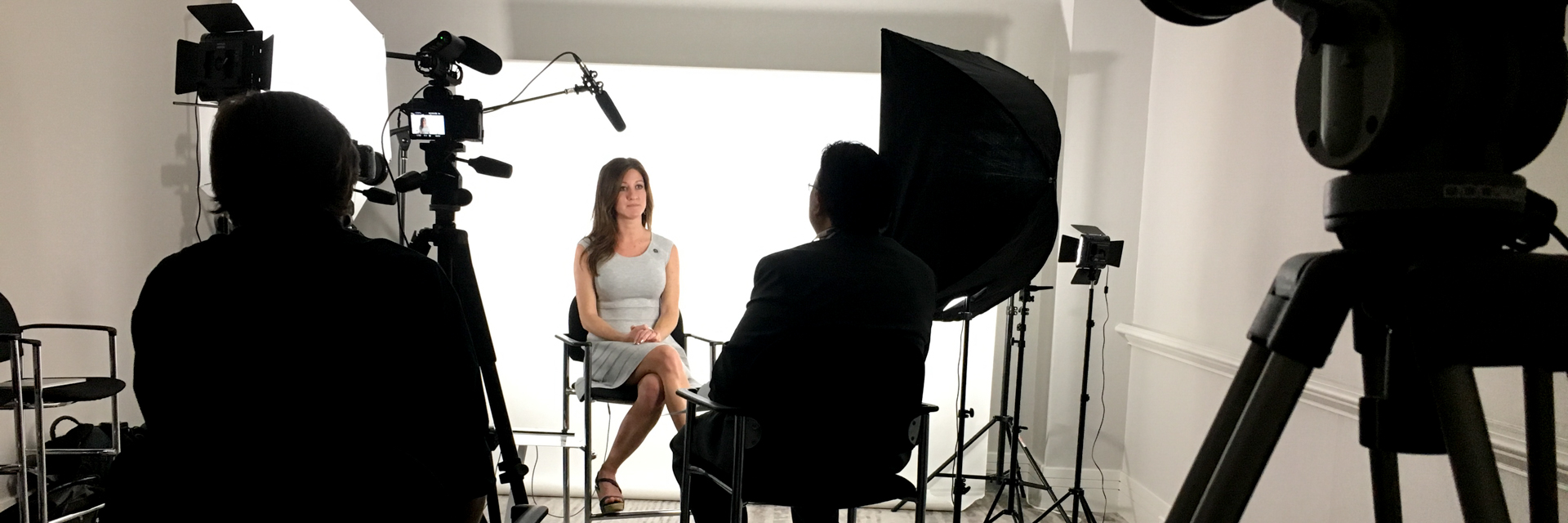 A beautiful woman sits for interviews in front of a pure white backdrop with lights, cameras, microphones and Dallas videographers surrounding her. This shows DTX Media's professional video production mobile studio set-up.