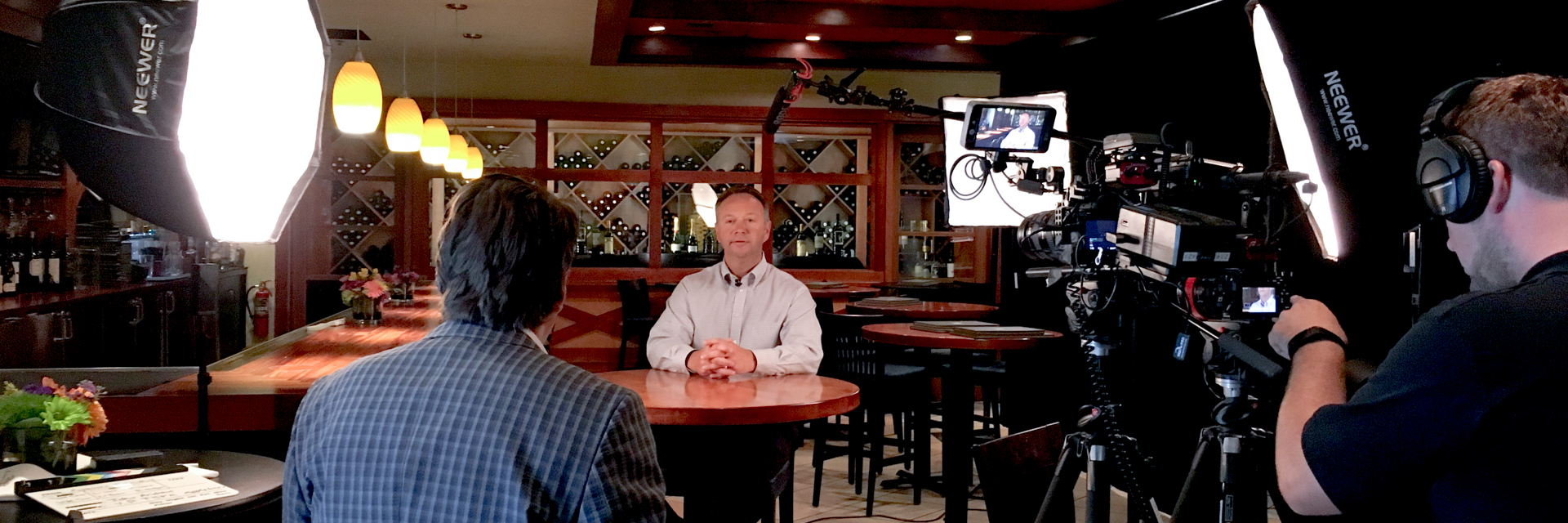 A behind the scenes look at DTX Media, a Dallas Interview Company filming. A man is sitting at a table for interviews with video lights and camcorders pointing at him.