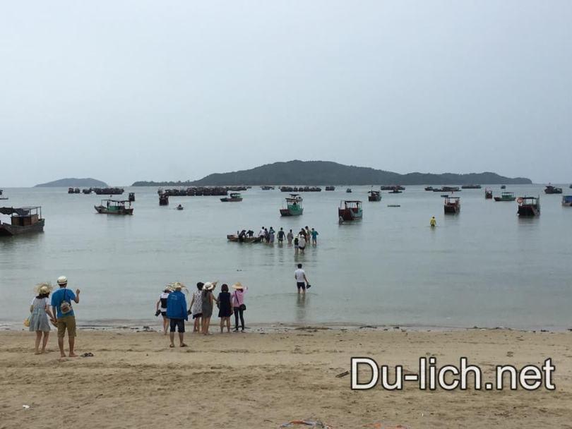 Lội xuống biển để đi ra tàu neo đậu ngoài lạch nước biển cạn