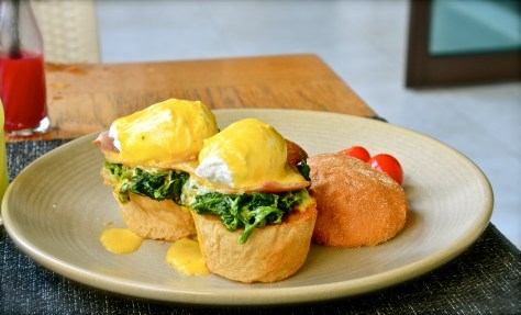 Egg benedict - poached eggs on a whole wheat biscuit with smoked turkey strips, creamed spinach topped with hollandaise sauce