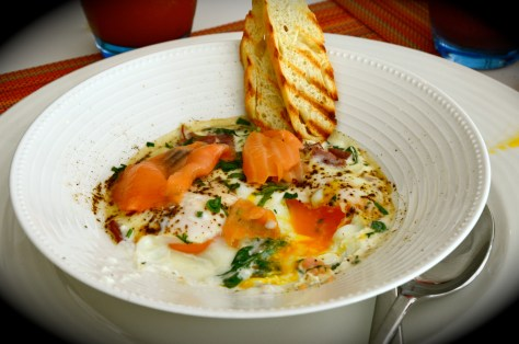 Eggs en Cocotte - AED 45 - Poached organic eggs, served in ramek ins with cheese, spinach leave s, smoked salmon, crispy bacon bits, toast & butter