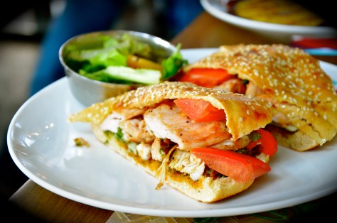 Roasted chicken Khameer sandwiches - AED 38 - Marinated chicken, onion marmalade, mint, basil, roasted peppers, tomato mixed with lemon vinaigrette and served with walnut pesto, sunderid tomatoes and gruyere cheese