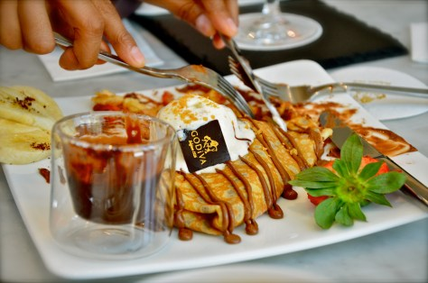 Strawberry/Banana Waffle - AED 48 - Traditional Belgian waffle served with fresh bananas and strawber- ries, drenched with Godiva's premium chocolate, and enriched with a scoop of vanilla ice cream