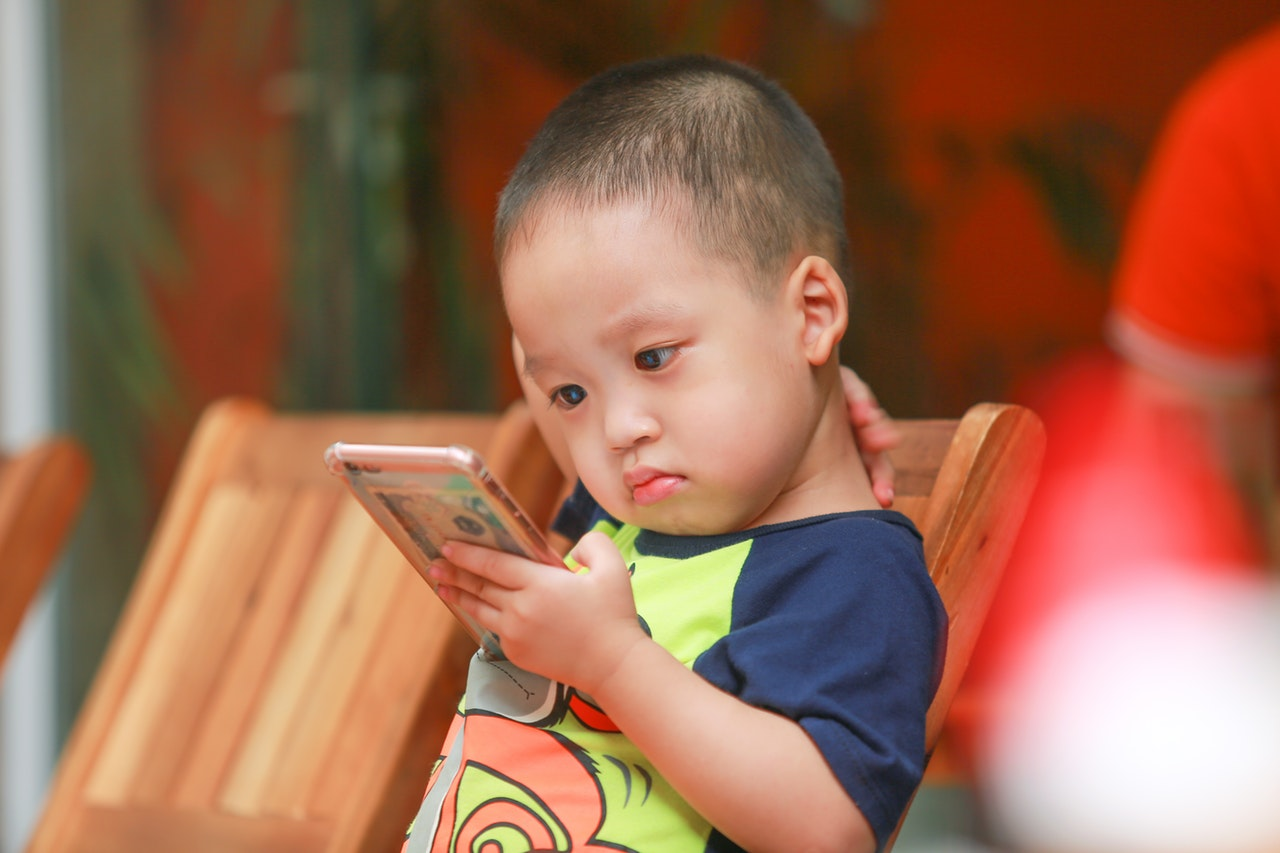 boy holding smartphone siting on chair 2181423