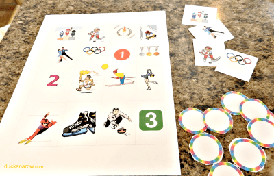 "O is for Olympics preschool ""bingo"" game by Ducks 'n a Row. Includes game board, bingo buttons and calling cards with instructions."