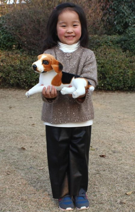 little girl with toy beagle dog
