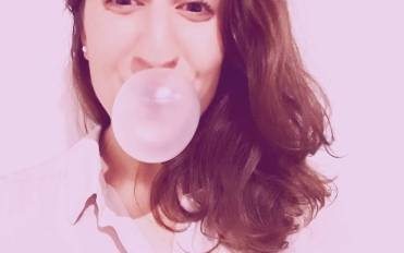 A girl blowing a balloon with bubble gum