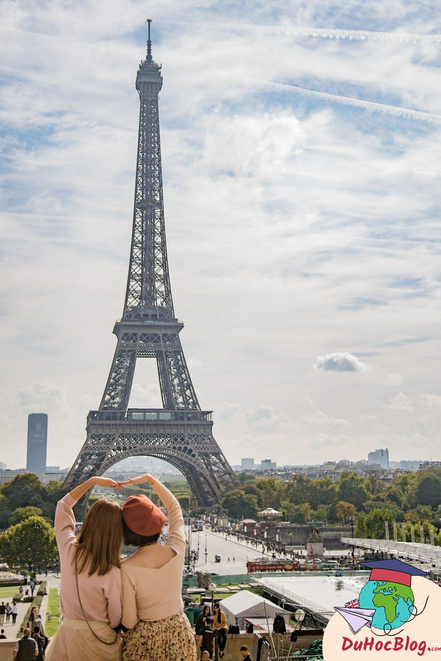 photo of two women posing in front of eiffel tower paris france during day time