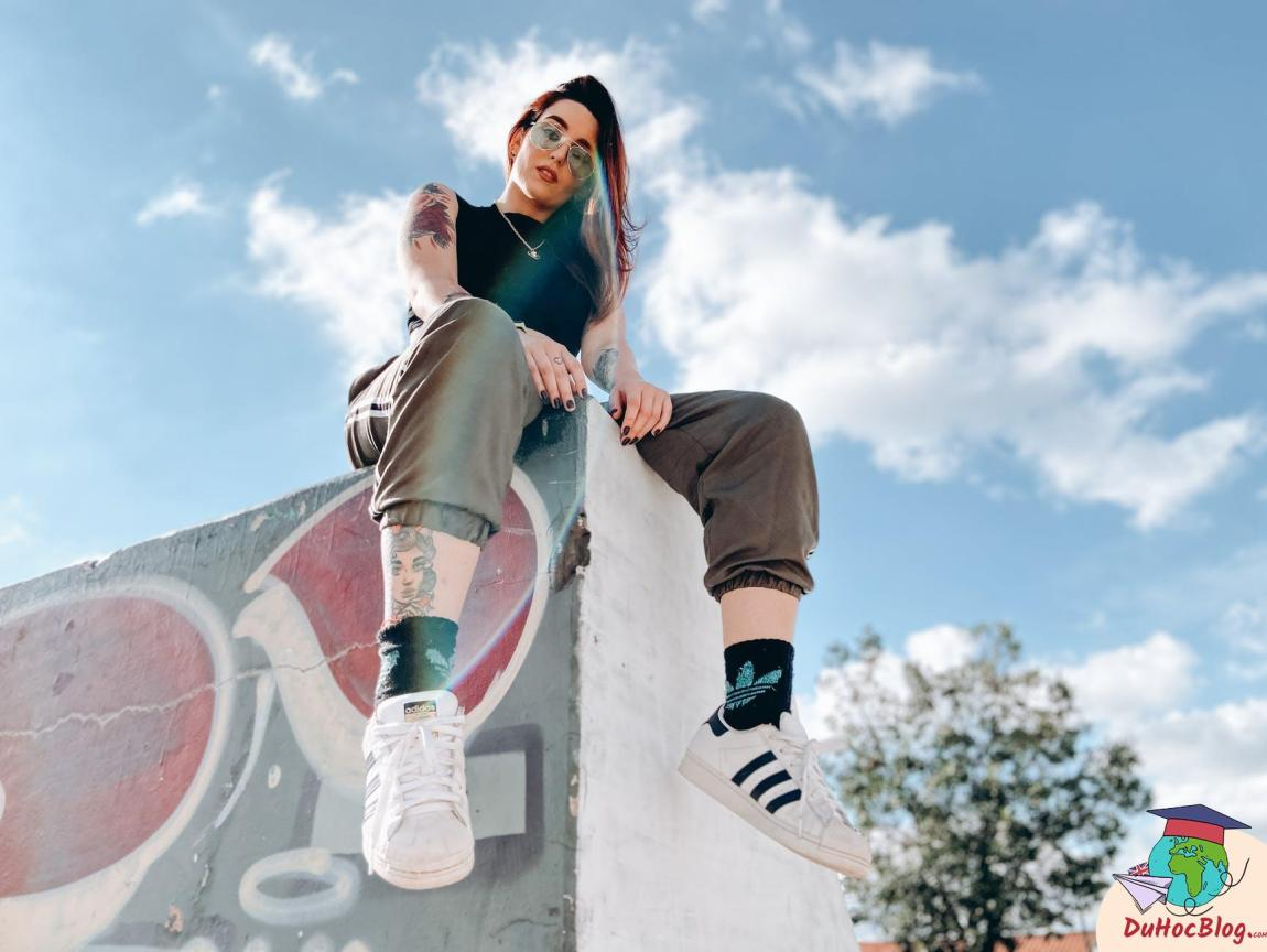 rebellious tattooed lady relaxing in skate park on sunny day
