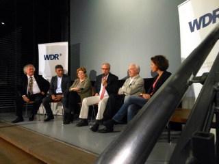 Die Talkrunde mit Zeitzeugen nach der Aufführung des Films (v. l.): Friedbert Barg, Ali Güzel (geb. 1966, kam 1976 mit 9 Jahren nach Deutschland), Annegret Finke (war bei Thyssen), Bernhard Dietz, Alt-OB Josef Krings und WDR-Moderatorin Ines Rothmeier.