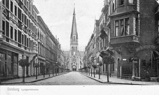 """Um das Jahr 1908 geht der Blick von der Mülheimer Straße in die Ludgeristraße  mit der gleichnamigen Kirche im Hintergrund. Man war darauf bedacht, durch Pflanzung von Bäumen den Wohnwert des werdenden Stadtteils zu steigern. Das wuchtige """"Hotel Restaurant Monopol"""" rechts bestimmt hier das Bild."""