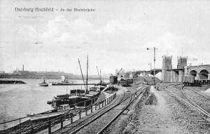 Kultushafen mit erster Eisenbahnbrücke nach Rheinhausen. Auf der anderen Rheinseite erkennt man die Krupp'schen Hüttenwerke. Die Eisenbahntrassen im Vordergrund gibt es zum Teil immer noch.