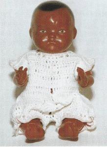 """Negerbabyen her er 17 cm høj og af typen """"nyfødt"""" - Babyen er af rødbrunt gennemfarvet celluloid. Hovedet er fast, og arme og ben bevægelige. De små øjne, håret og trutmunden er påmalede. Dukken er fra 1920erne. Og mærket med W i cirkel, derunder """"17""""."""