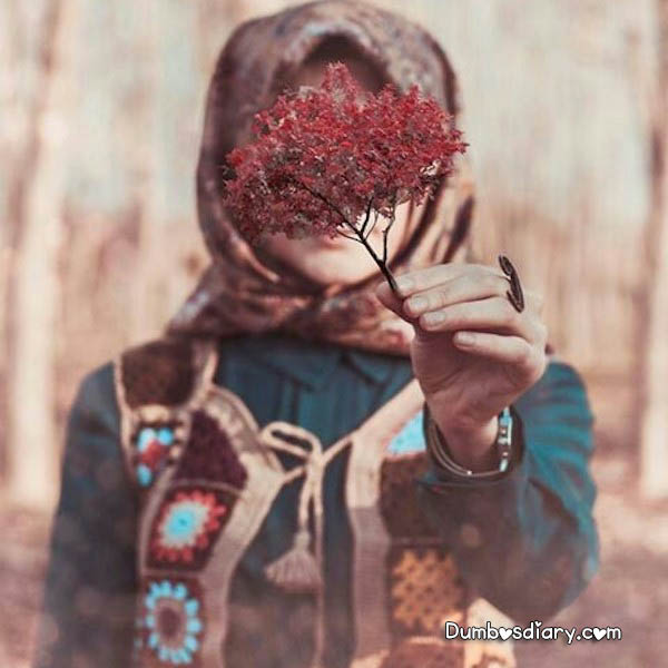 Beautiful hijabi girl hiding her face with flowers