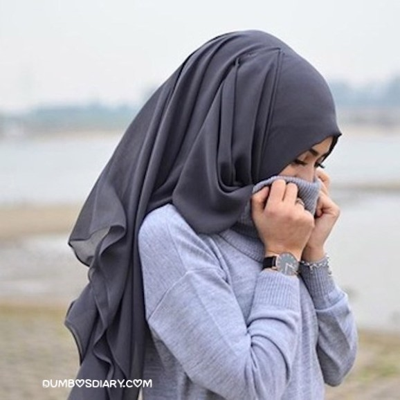 Cute muslim girl putting both hands on face to hide it