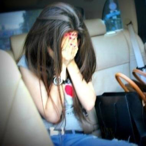 Girl in car hidding her face