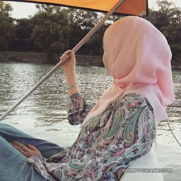 Hidden face in pink hijab sitting in boat
