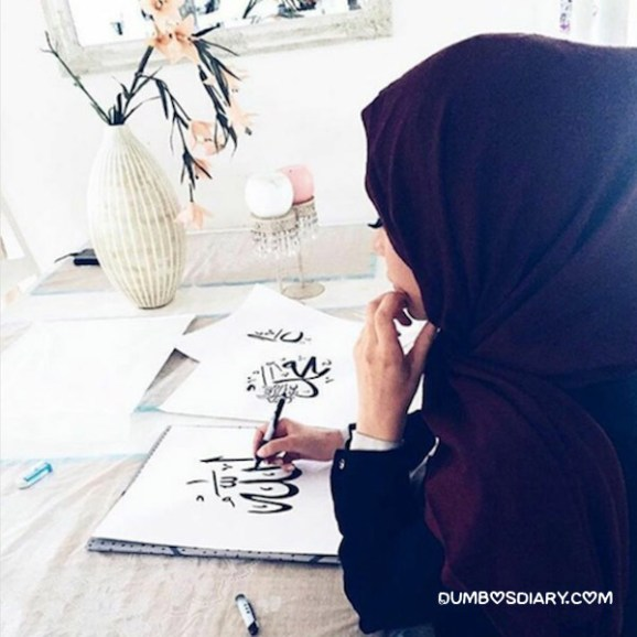 Innocent hijabi girl writing Allah