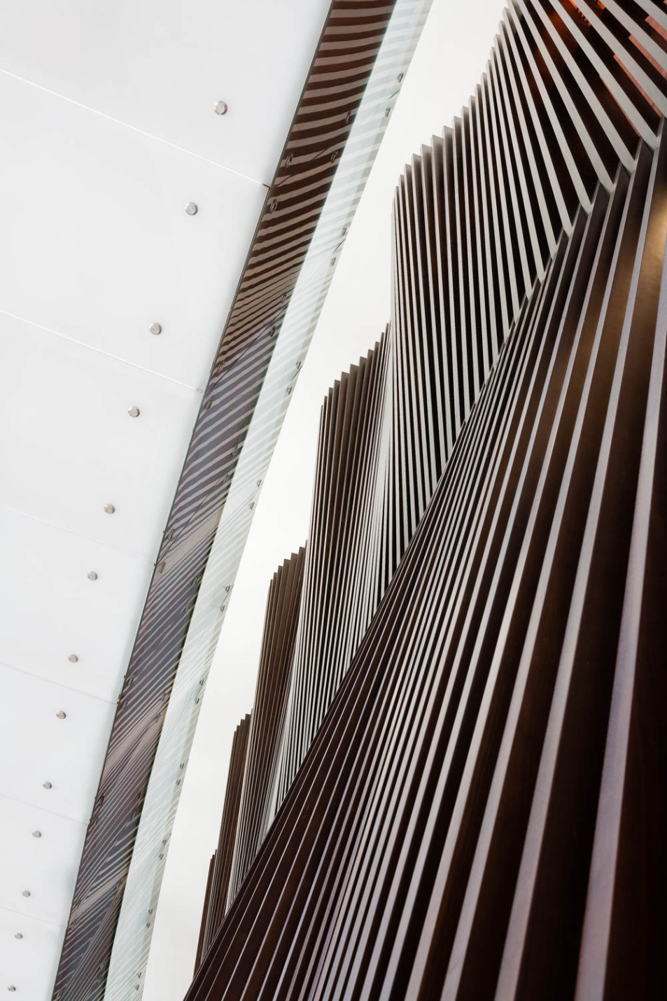 An architectural photograph showing the wooden sculptural wall and overhead walkway at the Address hotel in the downtown area of Dubai by photographer, Duncan Chard