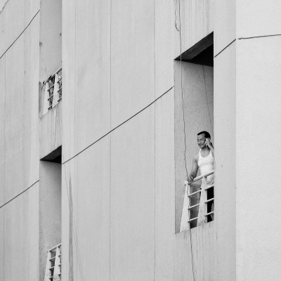 A worker makes a phone call on the balcony of his accommodation block, Dubai, UAE