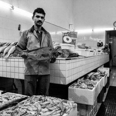 A fishmonger displays a local fish in his shop in Karama, Dubai