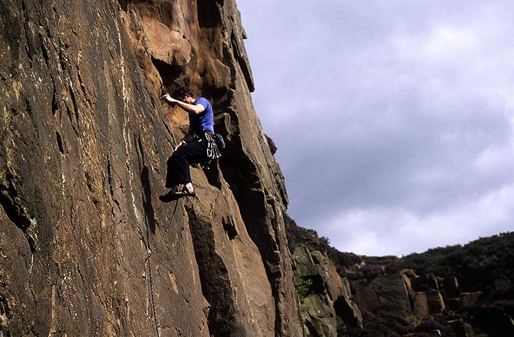 Climber traversing left from belay ledge