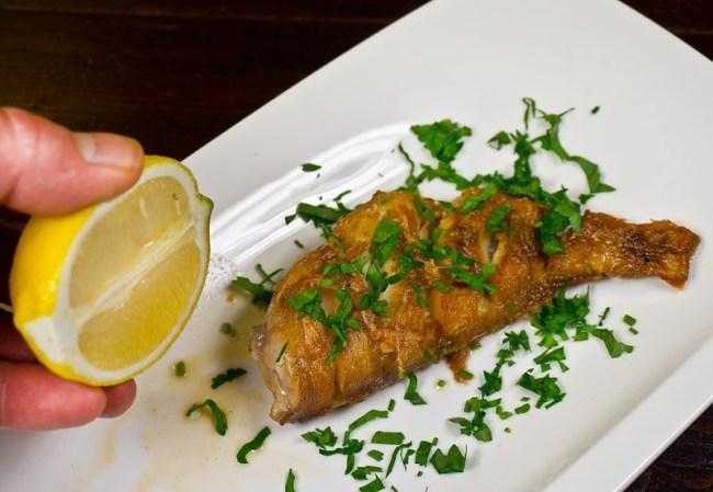 добавление петрушки и лимонного сока в рыбе