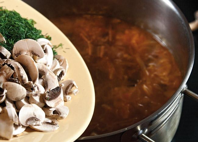 добавление шампиньонов и свежей зелени в сборную грибную солянку