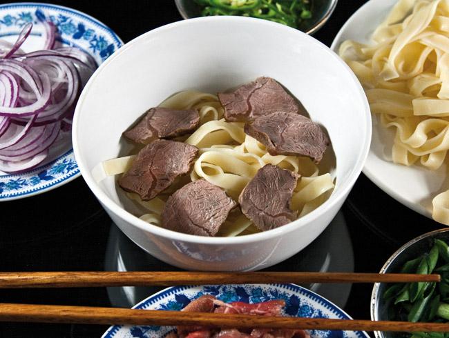 укладка лапши и отварного мяса в тарелку для супа по-ханойски фо-бо