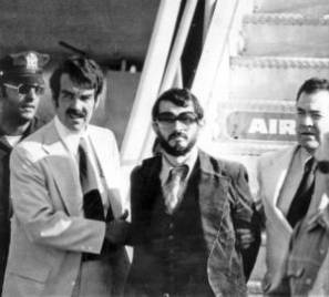 1976 photo of Zvonko Busic, with beard, being led from plane in custody of police at New York's Kennedy Airport after he and four companions returned from Paris to face charges of air piracy and murder. For obit.