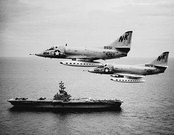 VA-146 A-4Cs over the Gulf of Tonkin in August 1964; USS Kearsarge steams below.