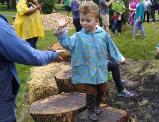 Happy preschooler gives high 5 in pop up playground by Jenifer Joy Madden