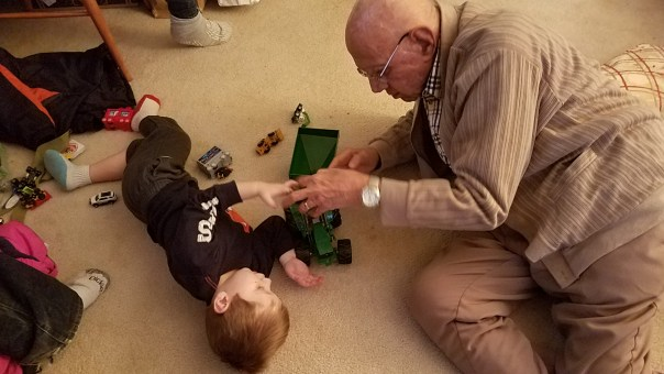 Great grandfather plays on floor with great grandson
