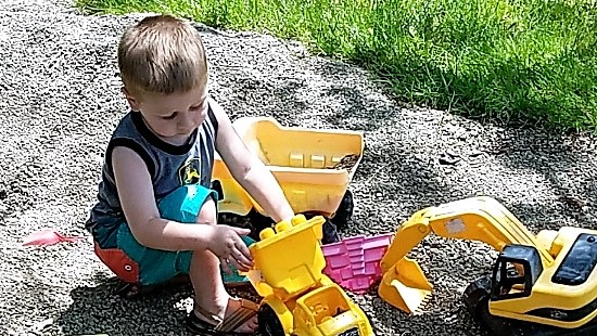 Boy playing outside with toy trucks