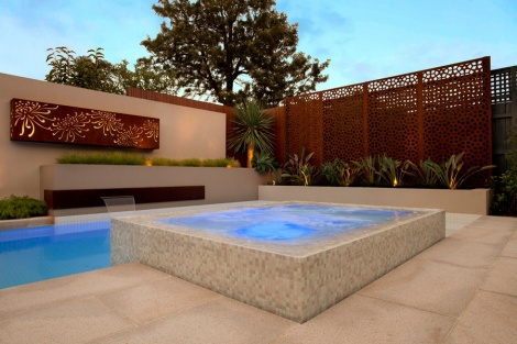 Custom narrow screens installed on top of a fence to create more height and interest for a pool enclosure fence. Other features include an art piece with back-light for added drama. Cor-ten steel