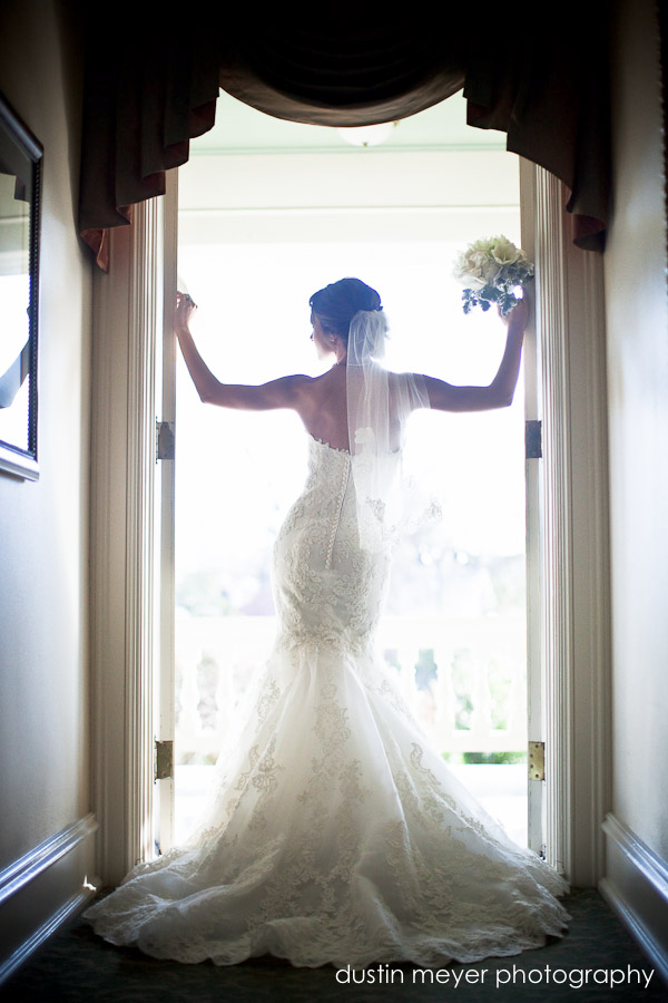 A bride poses for her bridal portraits in a doorway backlit with her wedding bouquet.