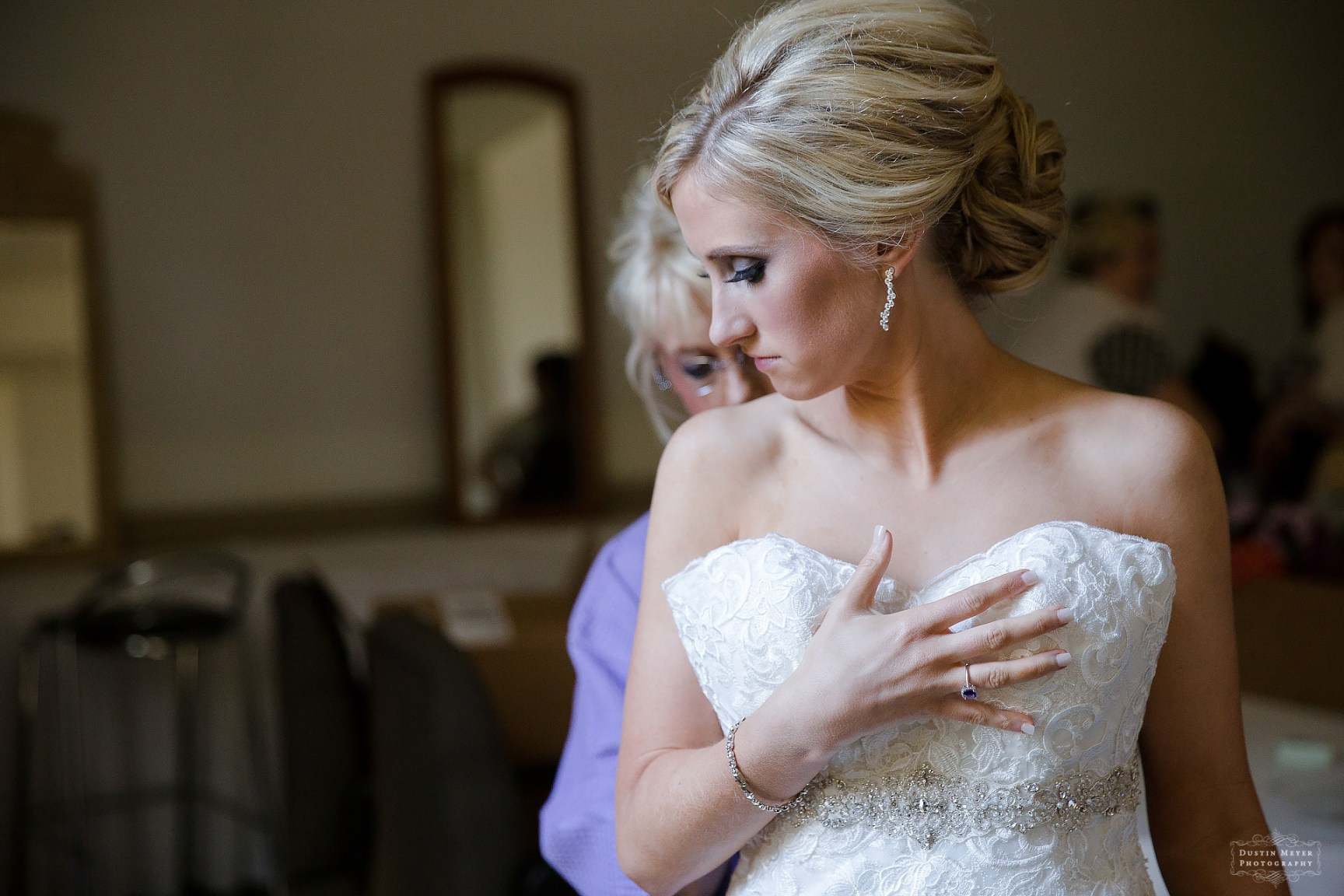 wedding day getting ready photo of bride and her mother in the bridal suite putting her strapless bridal wedding gown on