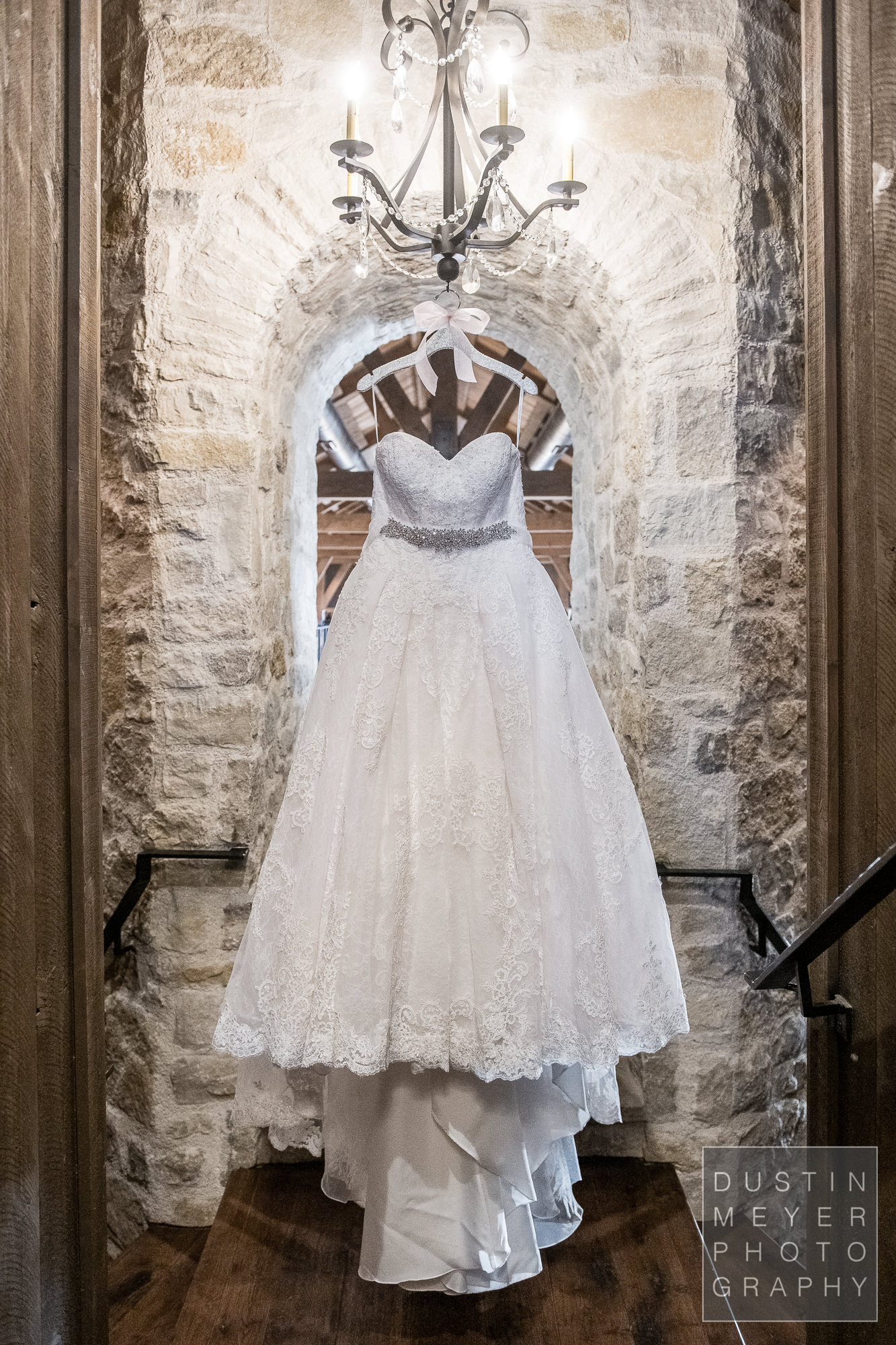 The gorgeous bridal gown hanging on display in a rustic setting