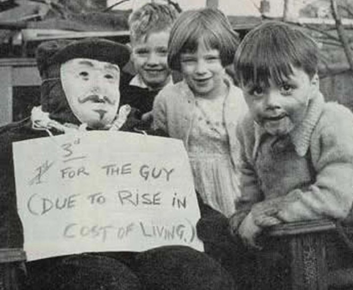 black and white photo of three children with a Guy Fawkes effigy holding a sign asking for a 'penny for the guy'