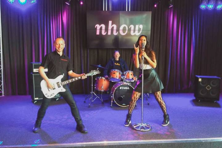 Group photo of Zarina fake singing, her husband Scanner pretending to play guitar and Graham Massey sitting behind the drum kit