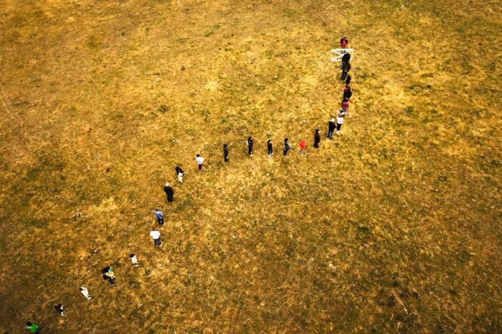 Foto door Spaanse fotograaf ruben martin de lucas waarop mensen in een nette rij voor een hekje in een weiland staan