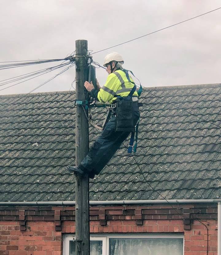 telefoonmonteur bovenop een paal in de straat om de verbinding te maken