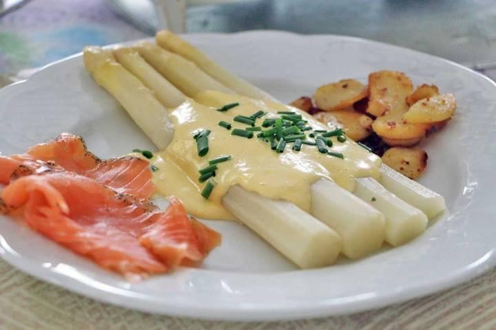 Bordje met witte asperges, gebakken aardappeltjes en plakken gerookte zalm
