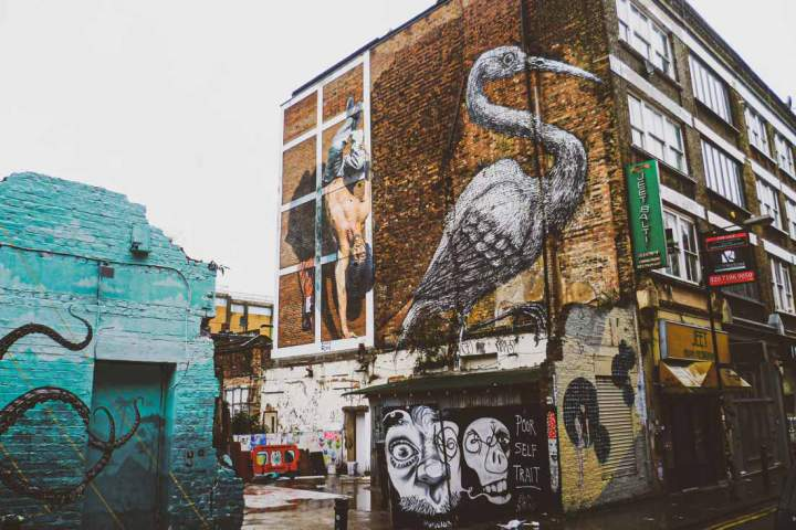 iconic Shoreditch street art by ROA on Hanbury Street of a giant crane (bird sacred to local Bengali) with next to it the mural by Martin Ron of a Tower of London Beefeater