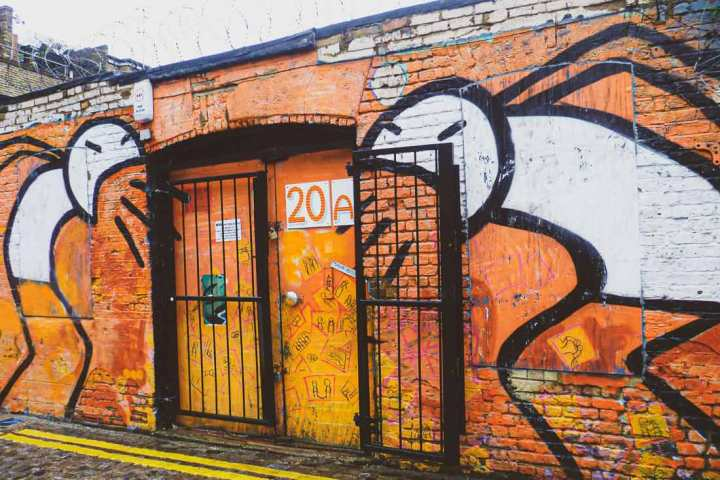 two large stick figures by artist Stik who are aggressively shouting at each other on a sidestreet of Brick Lane
