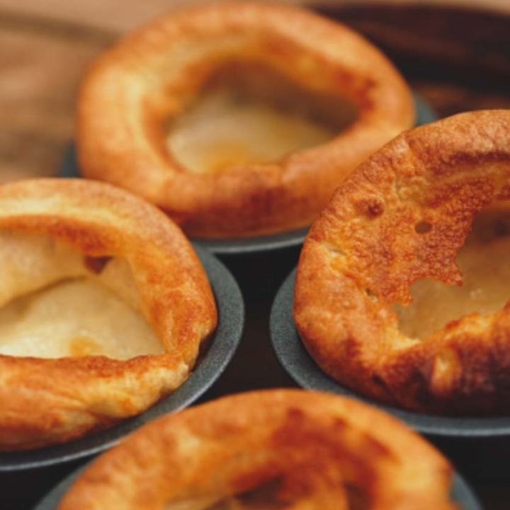 Yorkshire puddings being cooked in individual tins