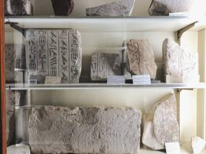 glass case with parts of stone remains with Egyptian hieroglyphics