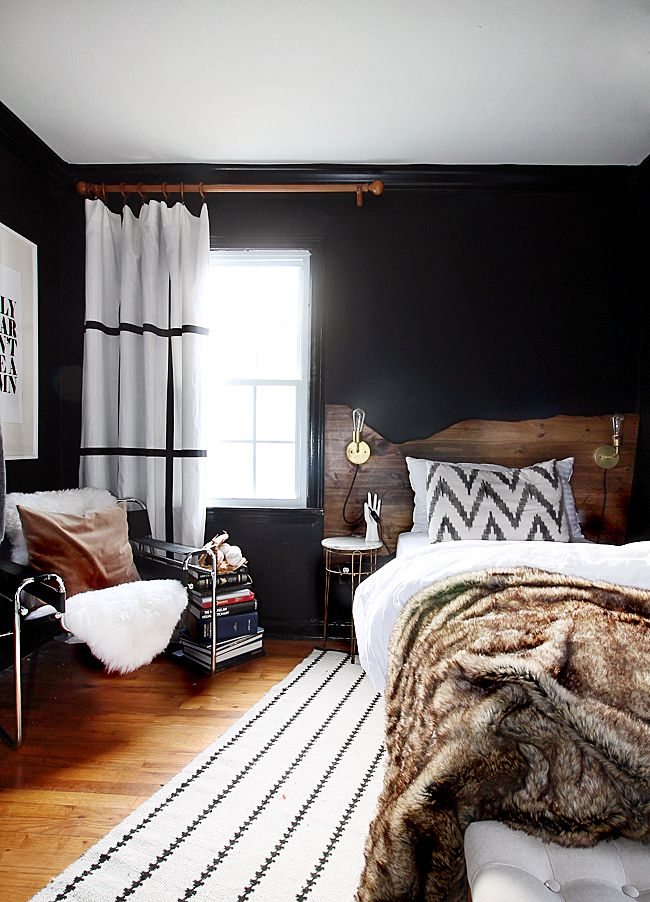 Bedroom with black wall and wood accents