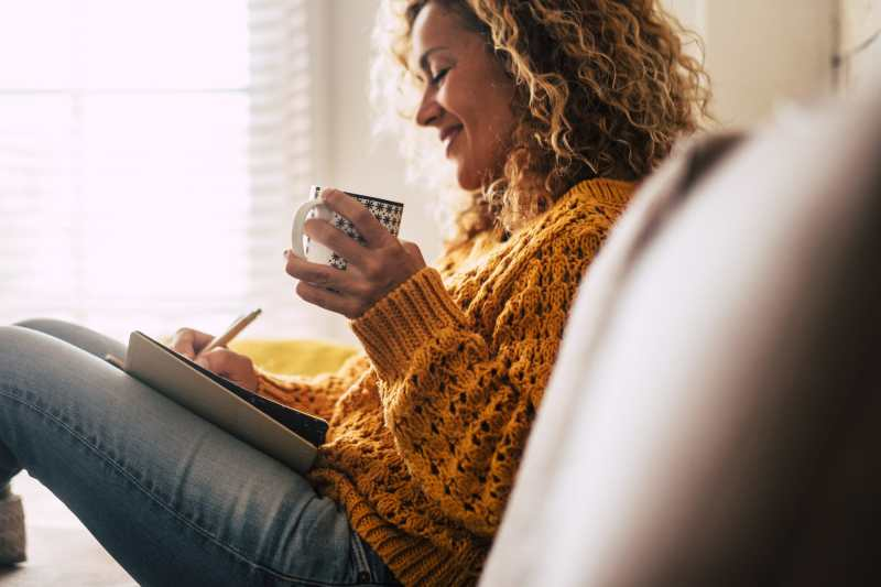 Happy cute lady at home write notes on a diary while drink a cup of tea and relax