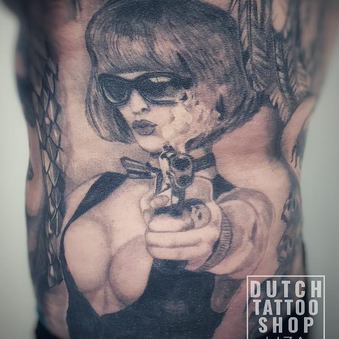 pin-up-sexy-vrouw-portret-zonnebril-pistool-borsten-tattoo